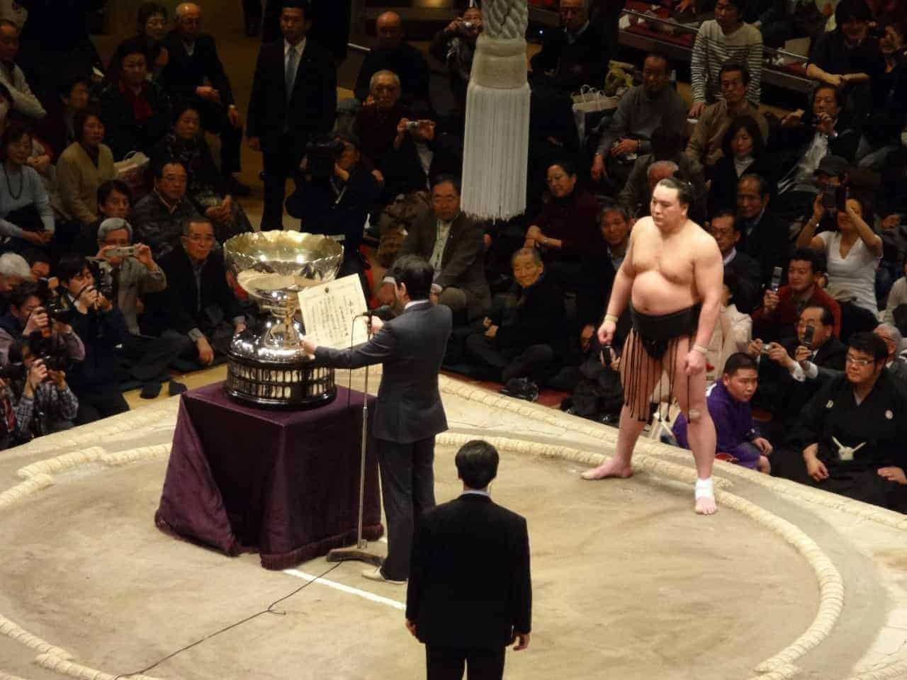 Sumo wrestler awarded trophy by Prime Minister of Japan, Abe.