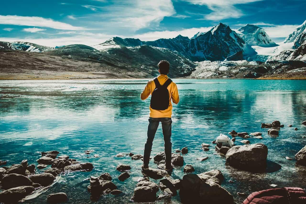 photo of man wearing backpack on rocks
